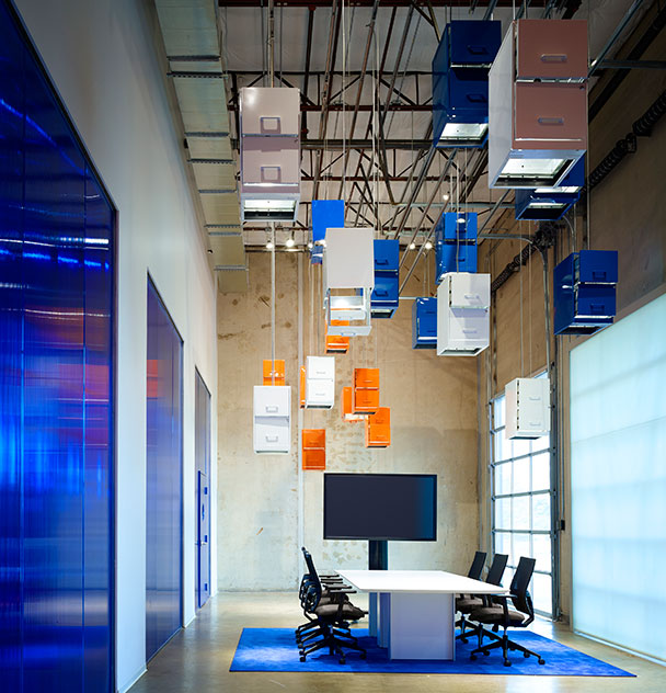 Pictured is the foyer to the Carrollton, Texas, location. File cabinets in the cloud represent the transition from storing information on paper to storing it digitally, in the cloud. The cabinets are color-coded with paint. White represents documents in use. Blue those searched for, and orange those lost forever. Photography: Scott McDonald (c) Gray City Studios